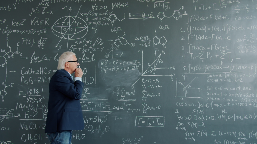 Intelligent professor in suit and glasses is working at project in college writing formulas on chalkboard wall thinking about science. People and education concept. | Shutterstock HD Video #1046982817