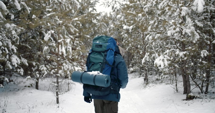 Bearded male hiker in warm clothing with backpack walking through winter forest. Handsome tourist in mirrored eyeglasses travelling outdoors. | Shutterstock HD Video #1047009367