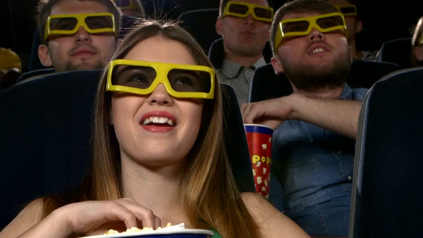 young people watching 3d movie at movie theater: comedy. Close up, Behind - the cheerful company of young people. different ages, popcorn