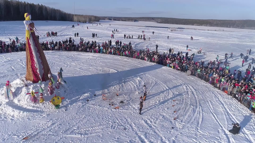 Circle of people which watch on scarecrow on celebration of Russian traditional holiday Maslenitsa (Shrovetide). Aerial | Shutterstock HD Video #1047104977