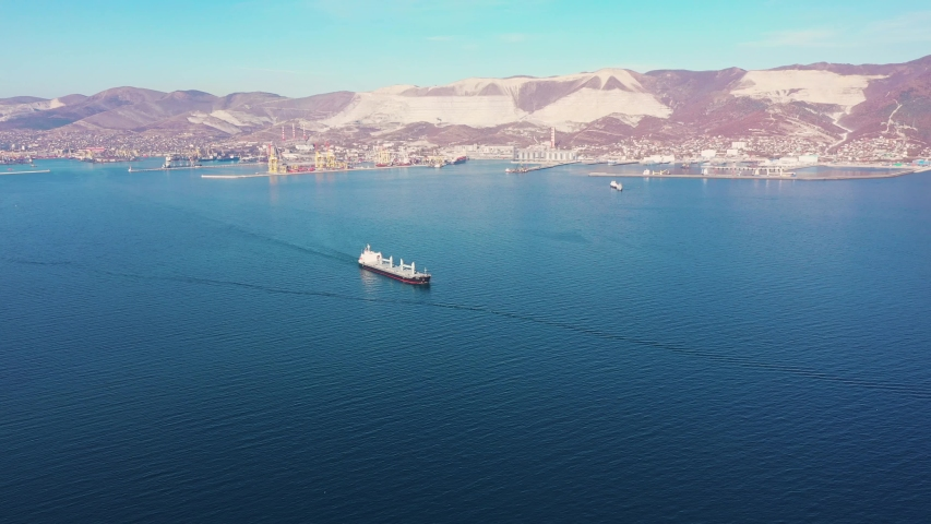 Aerial view following the ultra large cargo ship at sea leaves port at sunset. Top down drone footage of tanker. Concept of transport logistics, maritime. | Shutterstock HD Video #1047138397