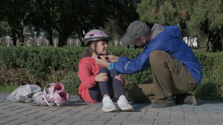 Father put a helmet. Thoughtful child daddy puts a helmet on girl`s head to makes sport in the park. | Shutterstock HD Video #1047174217