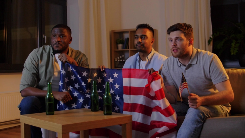 Friendship, sports and entertainment concept - happy male friends with american flag and beer watching tv at night at home | Shutterstock HD Video #1047212947