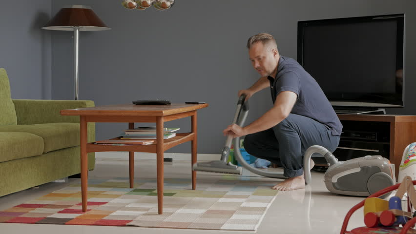 Man cleaning at home, under table with vacuum cleaner, 1 of 2