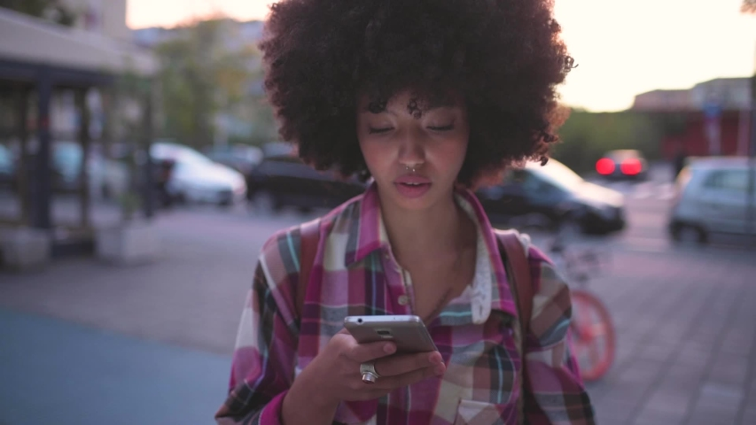 Young woman using smartphone and smiling at camera | Shutterstock HD Video #1048612387