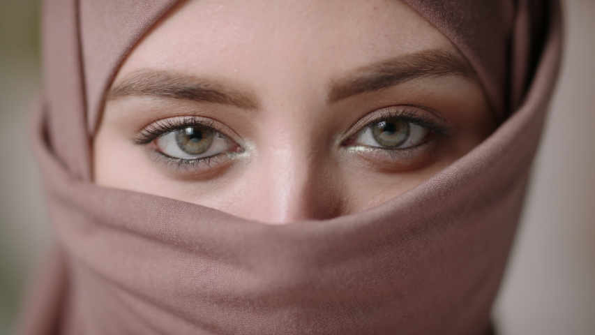 Face with natural make up of attractive muslim gir wearing traditional hijab scarf. Her brown and green eyes looking at camera - beauty, islam concept extreme close up 4k footage | Shutterstock HD Video #1048841467