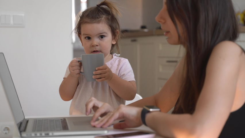 Mother working from home with baby toddler. Crying child and stressed woman. Stay home | Shutterstock HD Video #1048886137
