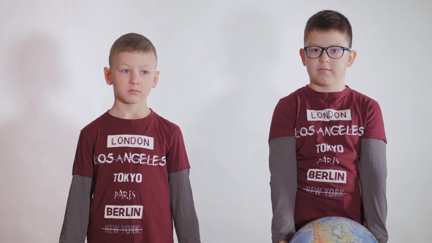 Boy holds a globe, a model of the planet Earth. Child is holding a sign with the inscription: TOGETHER WE ARE STRONGER. Boy is careful of the virus. Pandemic March 2020. Coronavirus. | Shutterstock HD Video #1049275807