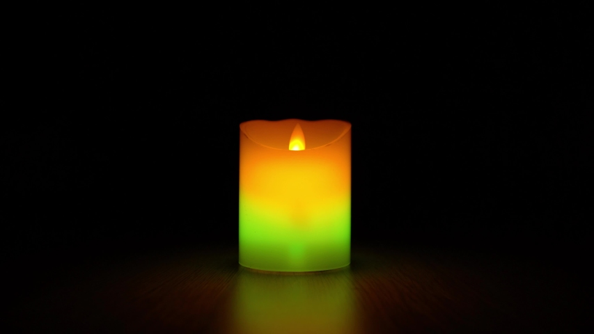 Multicolor led candle in the dark of night.  | Shutterstock HD Video #1049546737