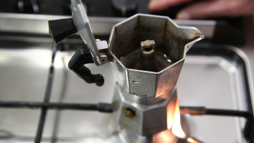 Moka pot on stove, Italain style coffee maker. Vapore caldo dalla pentola Moka sul fornello a gas portatile.    Shutterstock HD Video #1049549677