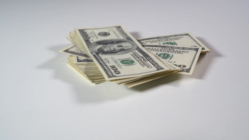 A bundle of dollar bills falls on a white table. Close-up | Shutterstock HD Video #1049640817