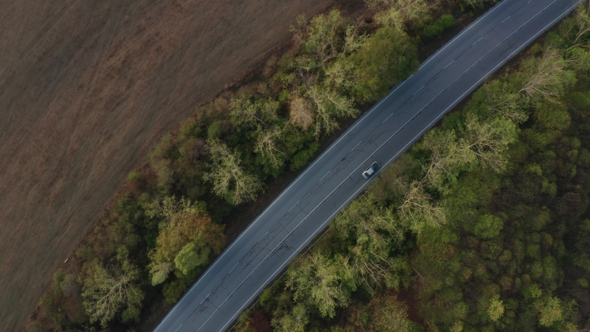 Drone flight over colorful autumn forest with road and cars in nice morning light, close up top view | Shutterstock HD Video #1049654557