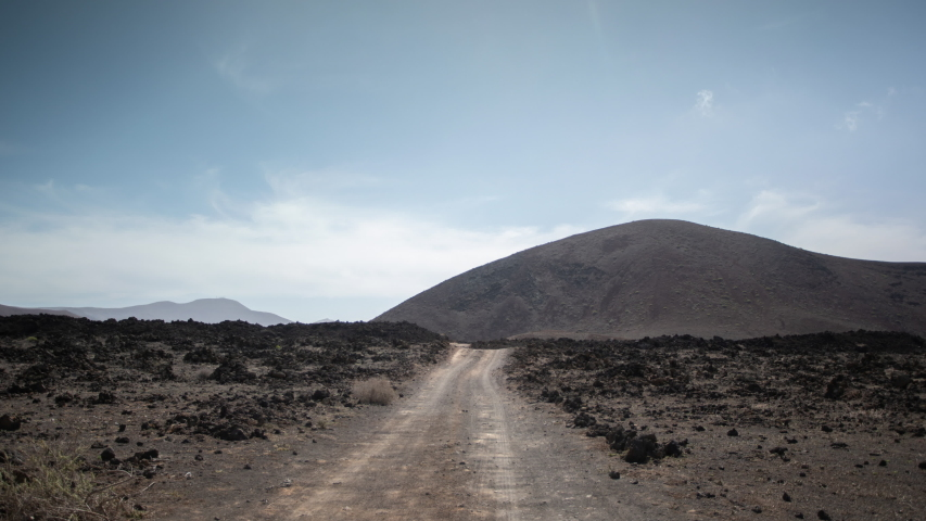 Timelapse of clouds passing over wild arid landscape with a gravel road of the Timanfaya National Park in Lanzarote. | Shutterstock HD Video #1049661307