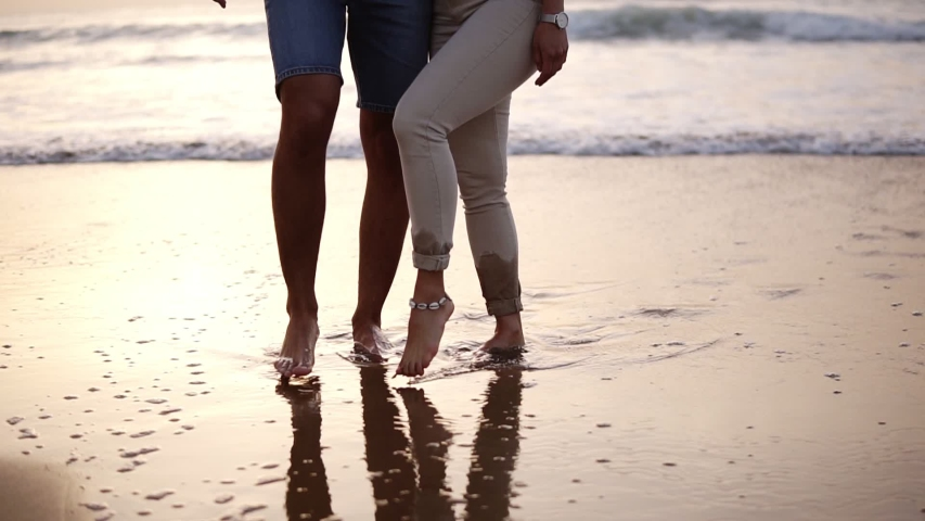 Couple of lovers man and woman paint with their feet on the wet sand heart. Cropped footage of loving couple on the sea coast. Slow motion | Shutterstock HD Video #1049661517