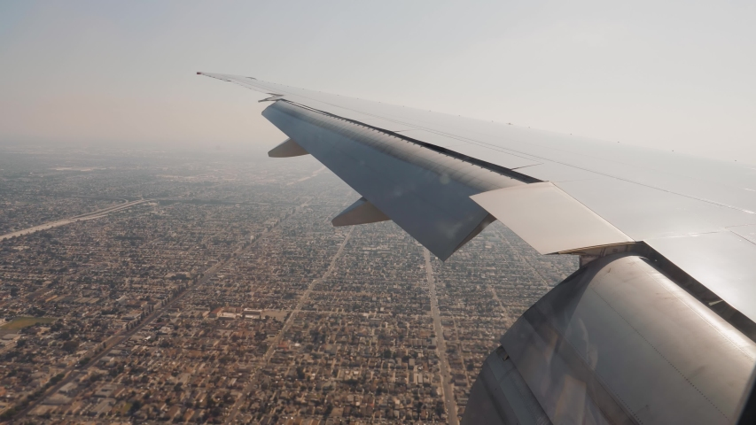 View from window of wing of the plane coming into land at airport in Los Angeles. Areas of city with a highway and many blocks with houses going into distance. Lowered flaps on wings to reduce speed | Shutterstock HD Video #1049703577