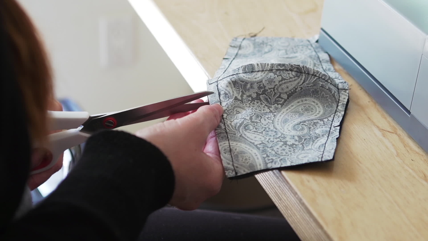 An experienced fashion designer working at home creating, stitching and sewing face masks from recycled fabric as a protection against viruses, disease and germs | Shutterstock HD Video #1049712397