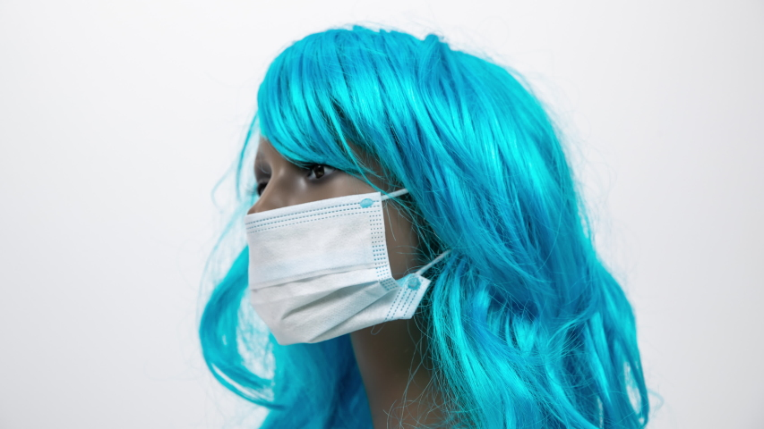 A mannequin head turning with blue hair wearing face mask for protection from viruses | Shutterstock HD Video #1049741137