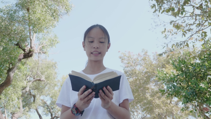 Asian girl reading a book  in the park.  | Shutterstock HD Video #1049790757