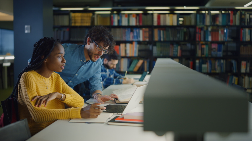 University Library: Gifted Black Girl uses Laptop, Smart Classmate Explains and Helps Her with Class Assignment. Happy Diverse Students Talking, Learning, Studying Together for Exams | Shutterstock HD Video #1049866987