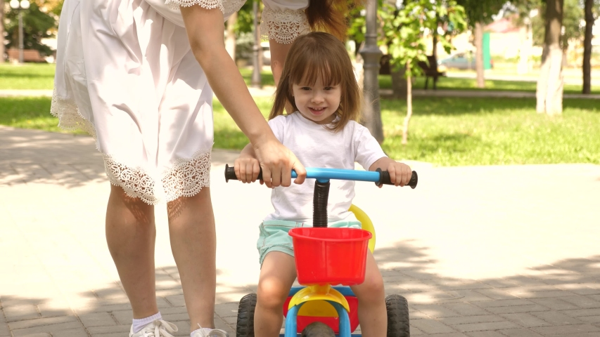 Happy mom teaches little daughter to ride bike. mother is playing with child outdoors. child learns to ride bicycle. concept of happy family and childhood. parents and little daughter walks in park. | Shutterstock HD Video #1049992147