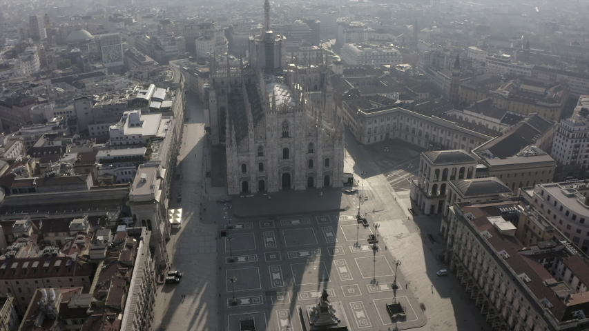 Daily life in Milan, Italy during COVID-19 pandemic. Milano, Italian city and coronavirus outbreak. Aerial view of Piazza Duomo. Urban square and buildings seen from drone flying in sky | Shutterstock HD Video #1050083197