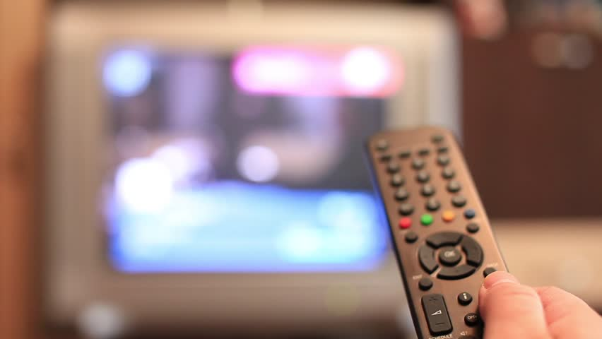 Timelapse of a man's hand switching channels on his TV with the remote control | Shutterstock HD Video #1050397