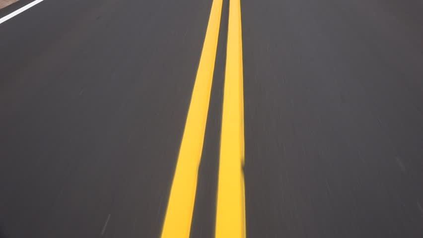 Time Lapse, Yellow double lines glow on newly paved road as they zip below vehicle, driver POV.  4K UHD 3840x2160