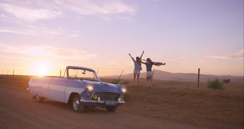 Girl friends dancing at sunset on road trip with vintage car RED DRAGON