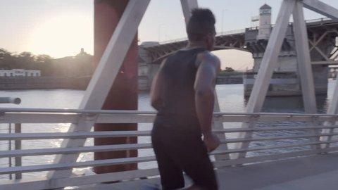 Male Athlete Runs Past Camera, Down A Pedestrian Bridge Along The Portland Esplanade (Slow Motion)