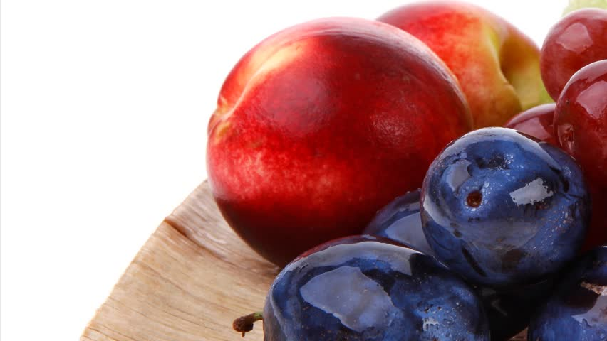 mixed set of fresh raw ripe fruits apple peach grape and plum on light wooden plate 1920x1080 intro motion slow hidef hd