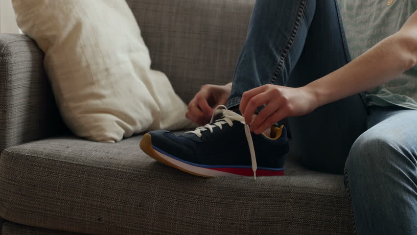 Young women tying fashion running shoes lacing on sofa before getting out