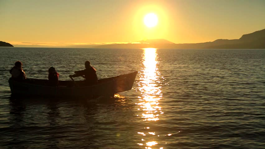 People paddling a boat with a beautiful sunset in the background. Sailing, kayaking, sport fishing and water skiing are popular sports during the summer at lake Villa Rica, in Chile.