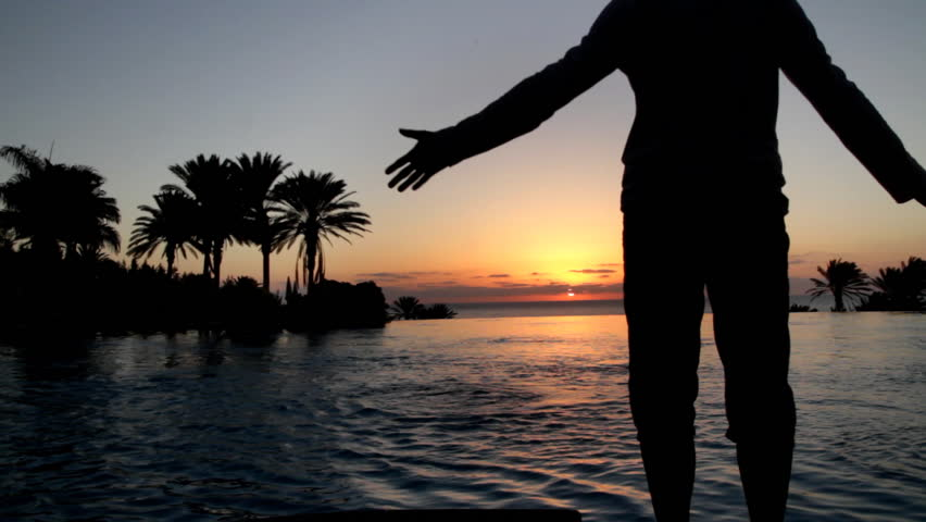 Man with arms wide open standing by the infinity pool during sunset