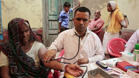 VRINDAVAN, INDIA - JUNE 14, 2015: A doctor conducts a medical examination of older women outdoors in central India.
