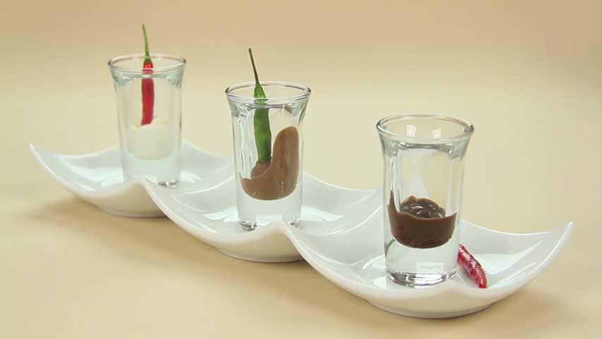 A chili being dipped into chocolate in a shot glass in a row of glasses.