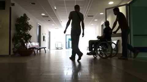 Backlighting of two men pushing a man in a wheel chair towards the light.
