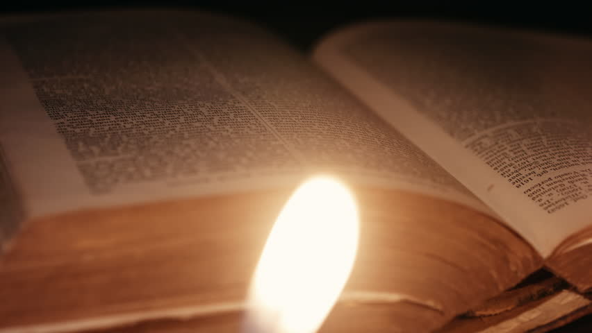 dolly shot of a man turning pages through an ancient book lit by candles