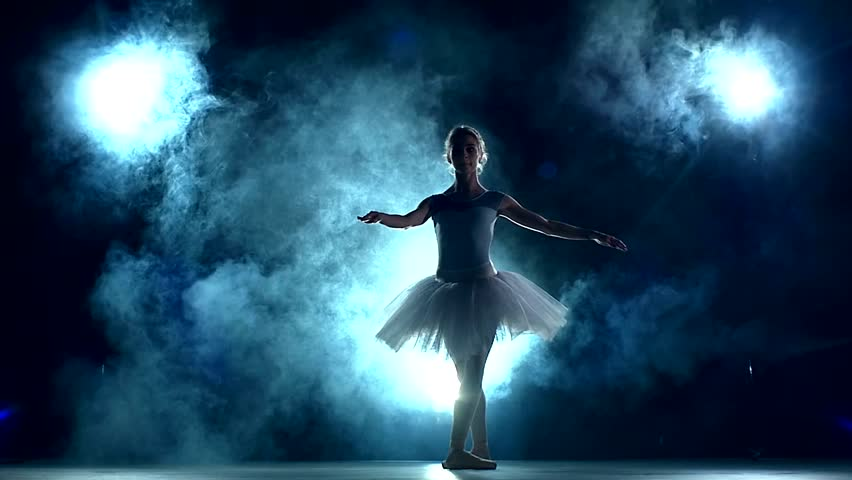 graceful ballerina doing a workout in the classroom. Smoke, fog, silhouette. ballet dancer in white tutu, girl in pointe, whirls around you, slow motion