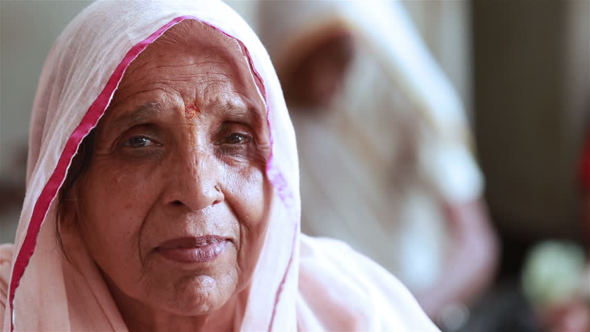 VRINDAVAN, INDIA - JULY 11, 2015: Elderly Indian woman in a traditional white scarf on head looking at the camera.