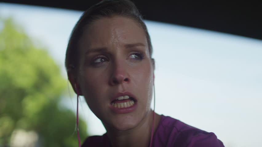 4K Female jogger out of breath looks around with a subtle smile on her face in slow motion, shot on RED EPIC