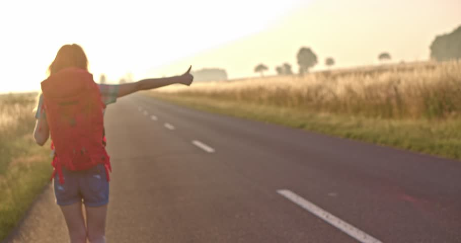 Traveler woman hitchhiking on a sunny road and walking. Young happy backpacker woman looking for a ride to start a journey on a sunlit country road. Slow motion, 120fps. 4K, DCi. Poland, Lower Silesia