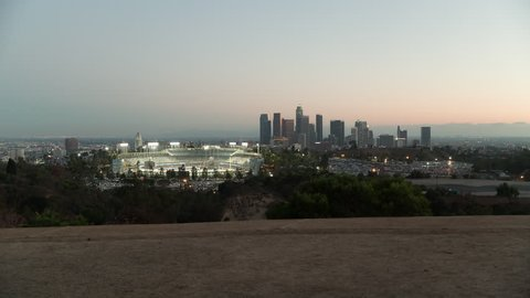 Hyperlapse of the Chavez Ravine, Dodger Stadium during sunset.  Stadium and parking lot full.  Traffic driving around stadium.    US Bank Tower, Los Angeles City Hall in shot.