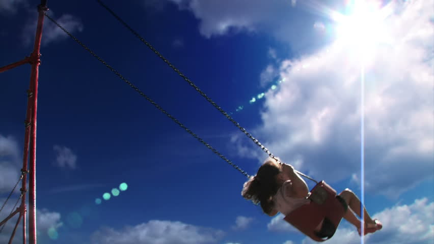 A young girl swings on a swing set in a playground  Low angle with the sky shown prominently.