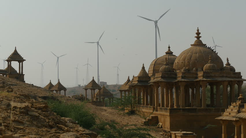 A large wind farm is visible behind ancient historical buildings nearby Jaisalmer, India.