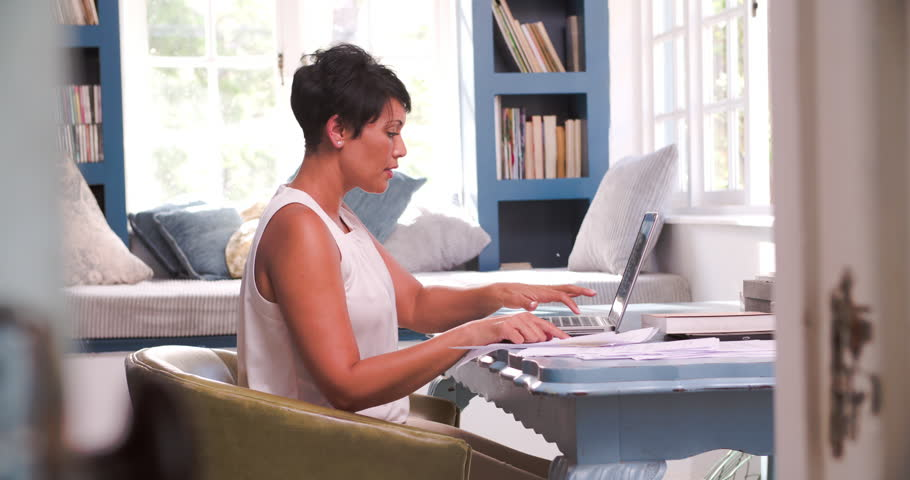working for home office. Mature Woman At Desk Working In Home Office With Laptop - 4K Stock Video Clip For I