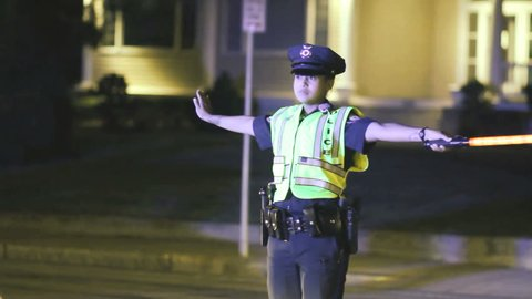 ATTLEBORO, MA - JULY 5: Female traffic cop directing cars at police scene on July 5, 2015.