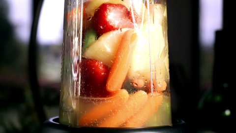 Fruit and Vegetable Juice prepared in Super Slow Motion.  Strawberry, Pineapple, Celery and carrots.