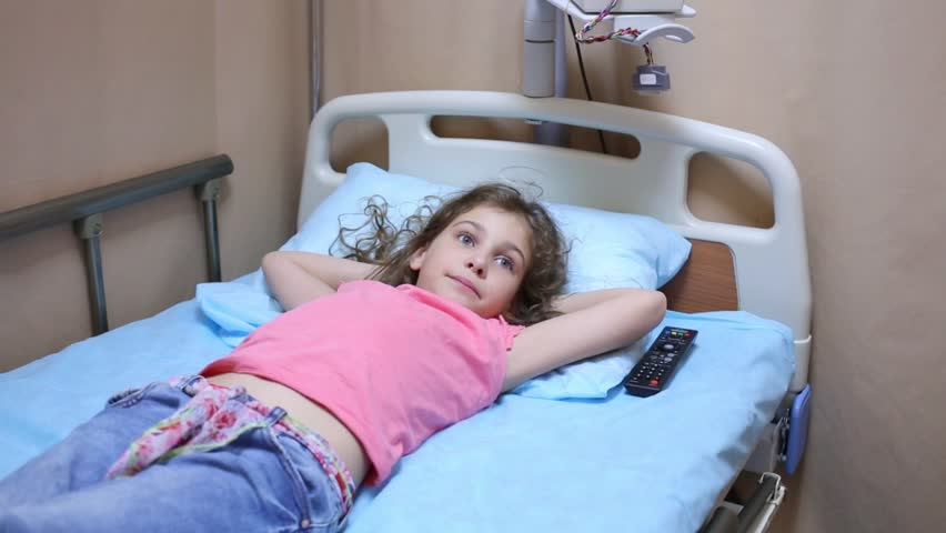 Health worker with remote control and little girl lying on bed in hospital ward. | Shutterstock HD Video #10705427