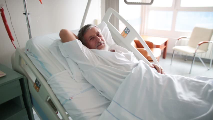 Patient at a hospital, lying on a bed in his room, resting and sleeping, doing much better after the surgery
