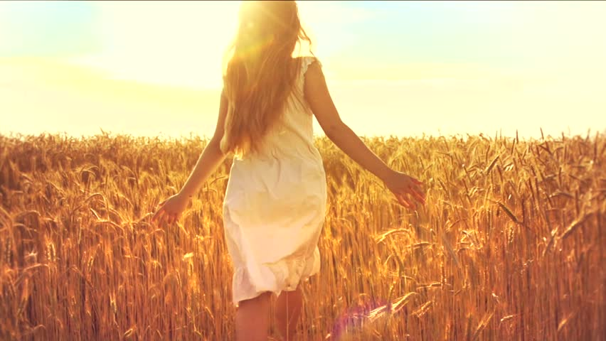 Beauty girl running on yellow wheat field over sunset sky. Freedom concept. Happy woman outdoors. Harvest. Wheat field in sunset. Slow motion 240 fps. Slowmo. 1080p full HD video footage